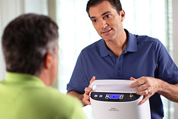 COPD Patient being trained how to maintain the SimplyGo Portable oxygen concentrator