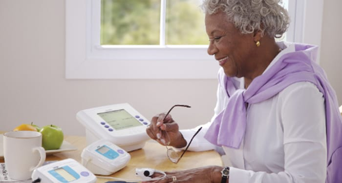 Lady sat at desk using a pulse oximeter